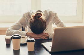 Exhausted woman sleeping at her desk, experiencing OSA symptoms