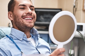 Man admiring his smile after receiving tooth-colored fillings